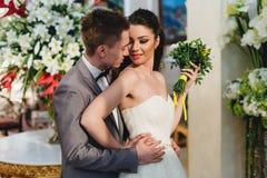 Nygifta personer som omfamnar på bakgrunden av blommor Royaltyfria Bilder