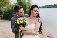 Nygifta personer som omfamnar på flodbanken Royaltyfri Fotografi