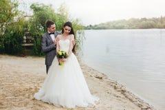 Nygifta personer som omfamnar på flodbanken Arkivfoto