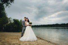Nygifta personer som omfamnar på flodbanken Royaltyfria Bilder