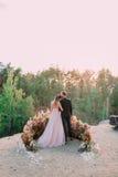 Nygifta personer som omfamnar på kanten av kanjonen med mjukhet och förälskelse tillbaka sikt Utomhus gifta sig Arkivbild