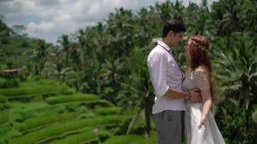 Nygifta personer som poserar på risterrassen i Bali Rymma händer som kramar romantiskt bröllop stock video