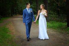 Nygifta personer som promenerar de trädgårds- banainnehavhänderna fotografering för bildbyråer
