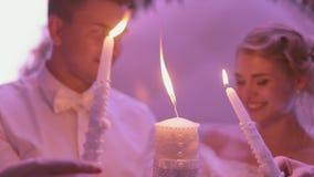 Nygifta personer som rymmer den brinnande stearinljuset stock video