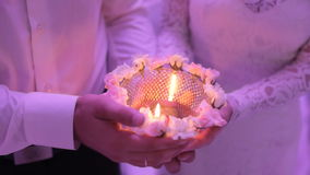 Nygifta personer som rymmer en stearinljus på bröllop stock video