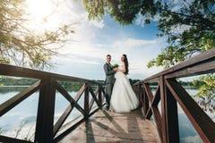 Nygifta personer som rymmer händer på flodpir Arkivfoto