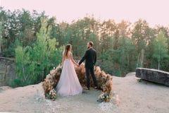 Nygifta personer som rymmer händer på kanten av kanjonen och paren som ser sig med mjukhet och förälskelse utomhus fotografering för bildbyråer
