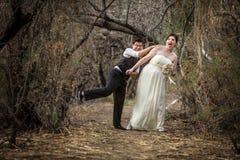 Nygifta personer som spelar i skog Royaltyfria Bilder