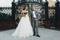Nygifta personer som står och rymmer händer Arkivfoton