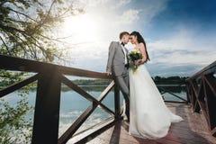 Nygifta personer som står på flodpir Royaltyfri Fotografi