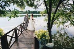 Nygifta personer som står på flodpir Arkivbild