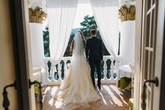 Nygifta personer som står på vita balkong- och innehavhänder, bakre sikt Bruden i en härlig vit klänning med långt hår royaltyfri fotografi