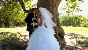Nygifta personer som står under ett träd lager videofilmer