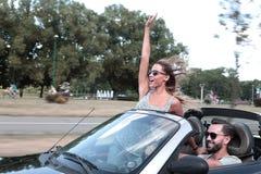 Nygifta personer som tycker om en tur i en cabriolet arkivbilder