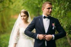 Nygifta personerna går i parkera på bröllopdagen Bruden och brudgummen Enjoying på bröllopdagen royaltyfria bilder