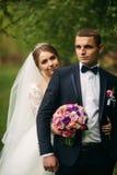 Nygifta personerna går i parkera på bröllopdagen Bruden och brudgummen Enjoying på bröllopdagen arkivbilder