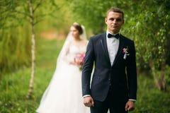 Nygifta personerna går i parkera på bröllopdagen Bruden och brudgummen Enjoying på bröllopdagen arkivfoton