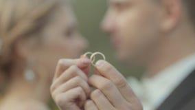 Nygifta personerna visar deras bröllop guld- cirklar lager videofilmer