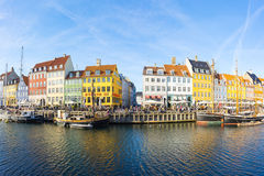 Nyhavn with colorful facades of old houses in Copenhagen, Denmar. Copenhagen, Denmark - May 1, 2017: Nyhavn with its picturesque harbor with old sailing ships Stock Image