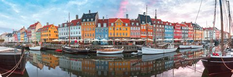 Nyhavn at sunrise in Copenhagen, Denmark. Nyhavn at sunrise, with colorful facades of old houses and old ships in the Old Town of Copenhagen, capital of Denmark stock image
