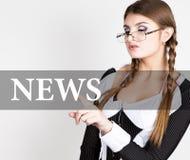 Nyheterna som är skriftlig på den faktiska skärmen den sexiga sekreteraren i en affärsdräkt med exponeringsglas, pressar knäppas  Royaltyfri Foto