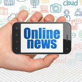 Nyheternabegrepp: Räcka hållande Smartphone med online-nyheterna på skärm Royaltyfria Foton