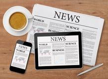 Nyheternasida på minnestavlan, mobiltelefonen och tidningen Arkivbilder