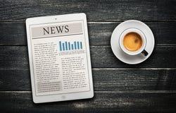 Nyhetsartikel på den digitala minnestavla- och kaffekoppen Royaltyfria Bilder