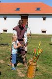 Nyiregyhaza, Венгрия Человек одетый в средневековых одеждах учит archery маленькой девочки Девушка снимает стрелки с смычком Стоковое фото RF
