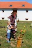 Nyiregyhaza, Ungarn Ein Mann, der in der mittelalterlichen Kleidung gekleidet wird, unterrichtet Bogenschießen des kleinen Mädche lizenzfreies stockfoto