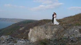 Nyligen gift gifta sig parställning nära en klippa som förbiser havet arkivfilmer