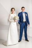 Nyligen gift par som poserar i studio över vit bakgrund Arkivbild