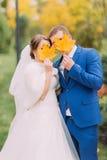 Nyligen gift par som utomhus poserar Ungdomarsom döljer deras framsidor bak höstsidor Royaltyfri Fotografi
