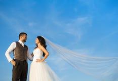 Nyligen gift parstående med blå himmel royaltyfri foto