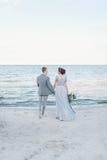 Nyligen-gifta sig framställning en promenera av stranden Arkivbilder