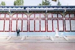 Nyligen-gifta sig står separat på bakgrunden av det gamla utställninggallerit på olika kanter av ramen Royaltyfri Fotografi