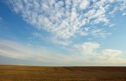 Nyligen plogat fält på en molnig himmel för bakgrund Arkivbild