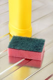 Nylon pan scourer. And detergent bottle on a stainless steel drainer Stock Images