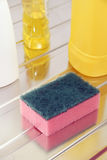 Nylon pan scourer. And detergent bottles on a stainless steel drainer Royalty Free Stock Photo