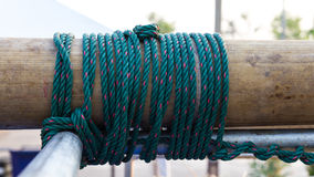 Nylon rope tied to a bamboo. Close up of green nylon rope tied to a bundle of bamboo to steel spiral together Stock Images