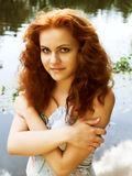 Nymph of the lake. Close-up portrait of a beautiful red-headed girl posing near the lake royalty free stock images