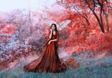 Nymphe puissante d'automne, reine du feu et déesse du soleil chaud, dame dans la longue robe de lumière rouge avec les douilles l photographie stock libre de droits