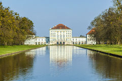 Nymphenburg castle grounds in Munich with reflection in lake, Ge Stock Photo