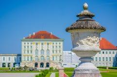 Nymphenburg, Deutschland - 30. Juli 2015: Palastgebäudeschuß vom künstlerischen Winkel mit sichtbarem hohem Abschluss der Skulptu Stockfoto
