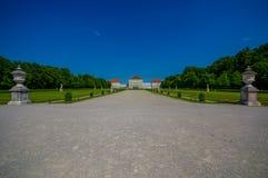 Nymphenburg, Deutschland - 30. Juli 2015: Schöner Palast, wie vom Abstand mit Statuen auf beiden Seiten von der Allee gesehen Lizenzfreie Stockbilder