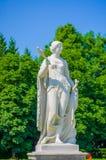 Nymphenburg, Duitsland - Juli 30, 2015: Het beeldhouwwerk van vrouw, mooie zonnige dag, groene gras en struiken in paleis tuinier Stock Foto