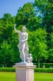 Nymphenburg, Duitsland - Juli 30, 2015: Het beeldhouwwerk van vrouw, mooie zonnige dag, groene gras en struiken in paleis tuinier Stock Afbeelding