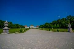 Nymphenburg, Duitsland - Juli 30, 2015: Mooi paleis zoals die van afstand met standbeelden aan beide kanten van weg wordt gezien Royalty-vrije Stock Afbeeldingen