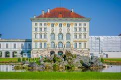 Nymphenburg, Germania - 30 luglio 2015: La facciata del palazzo come veduta avanti diritto attraverso dal lago, innaffia il cielo Immagine Stock Libera da Diritti