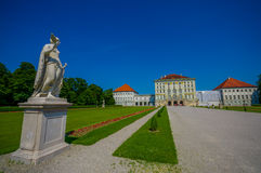 Nymphenburg, Germany - July 30, 2015: Beautiful palace as seen from distance with statues on both sides of avenue leading up to bu Stock Images